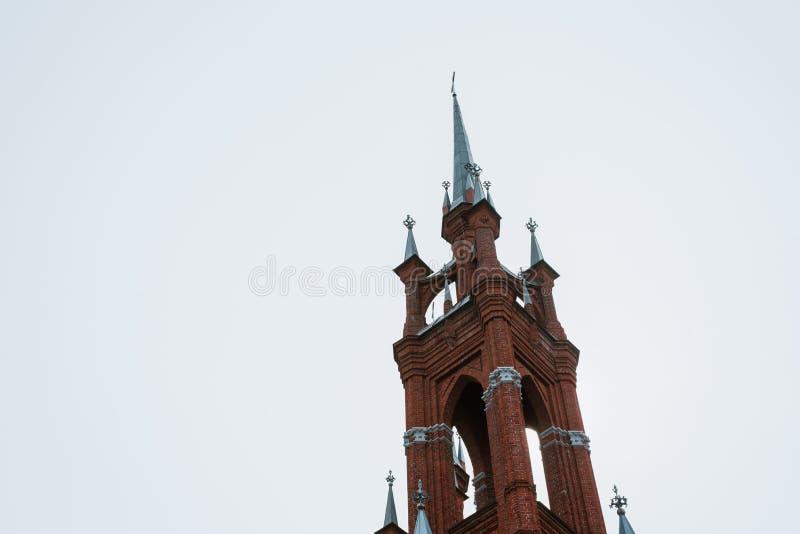 Kyrkan ?r av r?d tegelsten, med kors och tunna f?nster fotografering för bildbyråer
