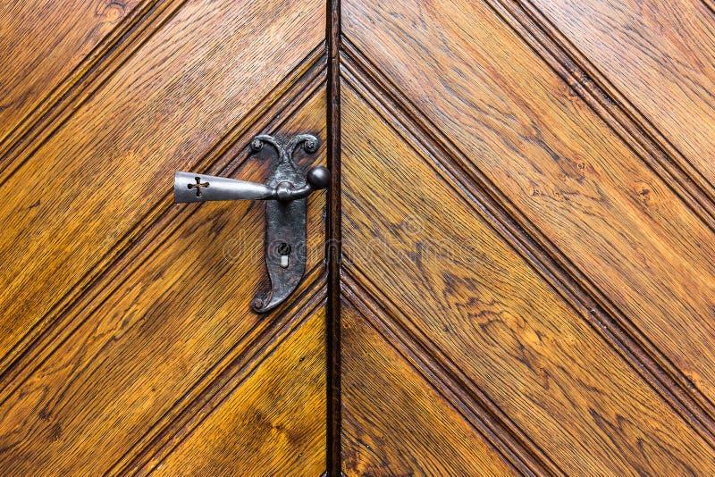 Kyrklig dörr för antikvitet med knoppen för dörrhandtag som göras av järntexturbakgrund arkivbilder