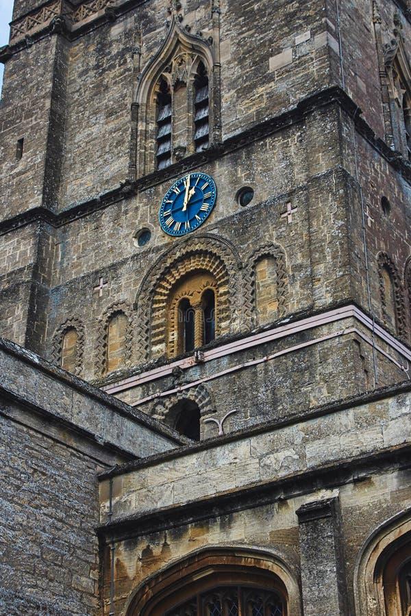Kyrkligt klockatorn med den blåa klockaframsidan i den klassiska stilen i England royaltyfria bilder