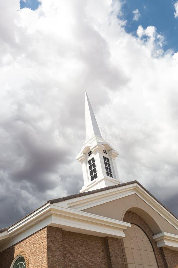 Kyrkligt kyrktorntorn nedanför illavarslande stormiga åskvädermoln royaltyfria foton