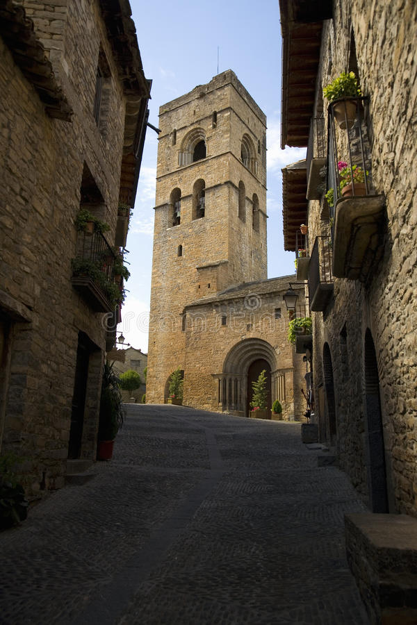 Kyrkligt torn på Plazaborgmästaren, i Ainsa, Huesca, Spanien i Pyrenees berg, en gammal walled stad med bergstoppsikter av Cinca  arkivfoto