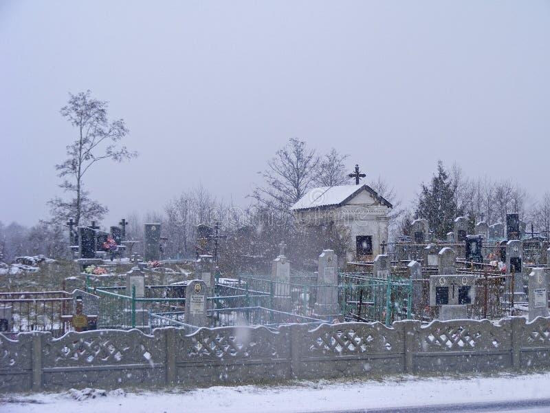 kyrkogård Gammal katolsk kyrka eller ortodox kyrka Lantligt landskap i snöig vinterplats royaltyfri bild