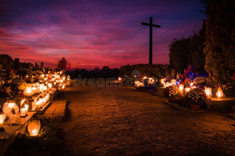 Kyrkogård med rörda konturspökar och ett kors sent i aftonen royaltyfria foton
