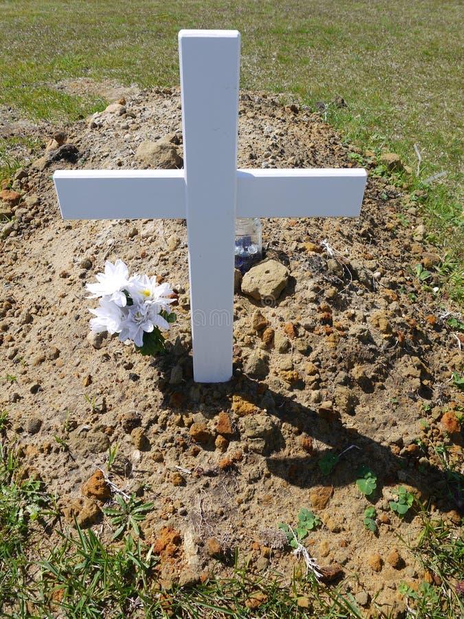 Kyrkogård: ny grav med det vita korset royaltyfri foto