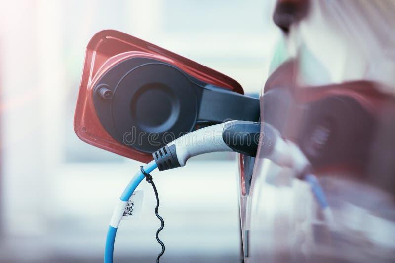 Kyrktaga en elbil med tillförsel för maktkabel som in pluggas royaltyfria foton