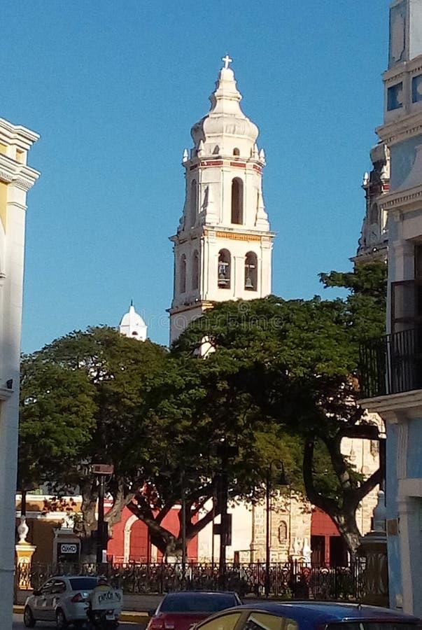 Kyrktorn av en katolsk kyrka som står högt ovanför parkera i Campeche, Mexico royaltyfria bilder