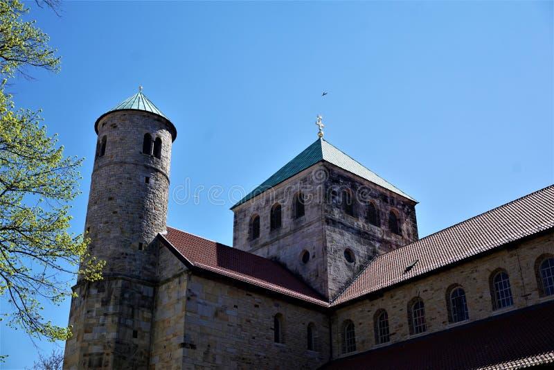 Kyrktorn och trädfilialer framme av Sts Michael kyrka i Hildesheim royaltyfri fotografi
