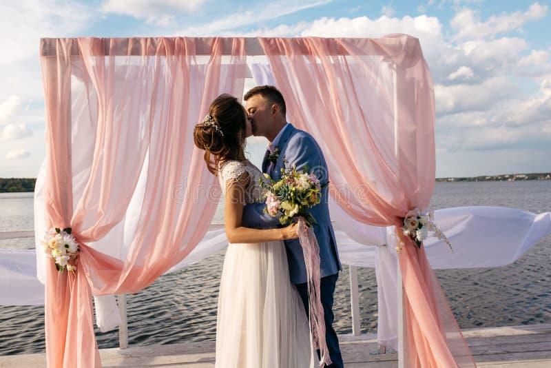 Kyss av bruden och brudgummen, på pir under bröllopbågen royaltyfri foto