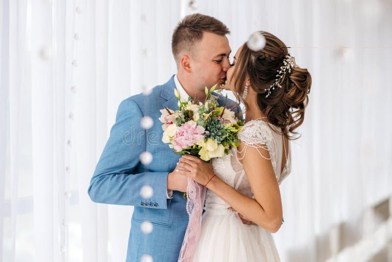 Kyss av brudgummen och bruden i rummet arkivbilder