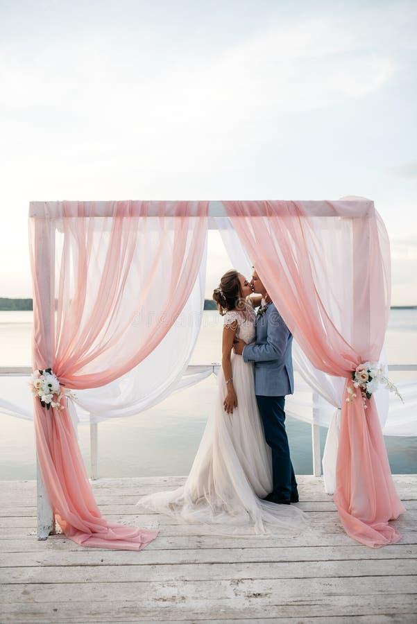 Kyss av den utomhus- bruden och brudgummen arkivbild