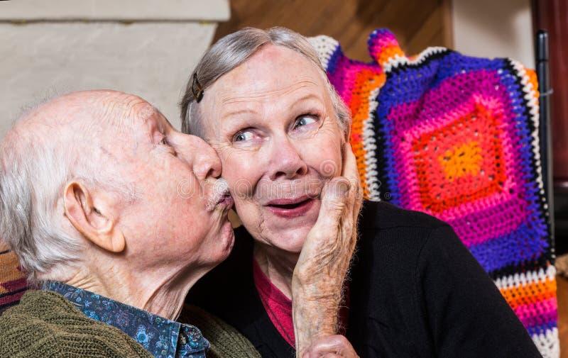 Kyssande äldre kvinna för äldre gentleman på kind royaltyfri fotografi