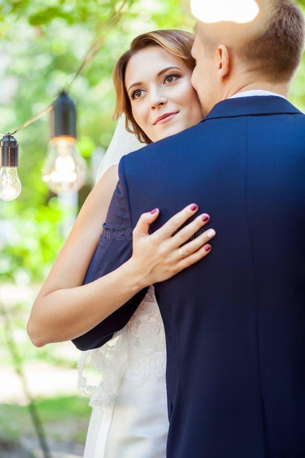 Kyssande attraktiv brud för stilig brudgum i sommarträdgård fotografering för bildbyråer