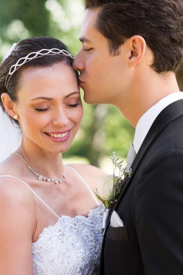 Kyssande brud för brudgum på huvudet i trädgård royaltyfri foto