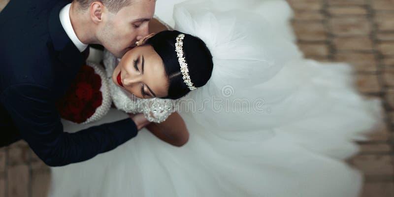 Kyssande brunettbrud för romantisk brudgum på halsen royaltyfria bilder
