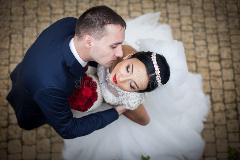 Kyssande brunettbrud för romantisk brudgum på halsen, skott från abo royaltyfria foton