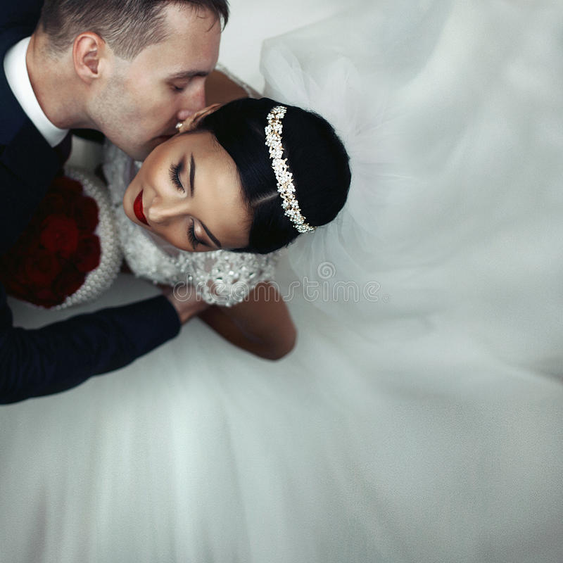 Kyssande brunettbrud för romantisk brudgum på halsen, skott från abo arkivbild