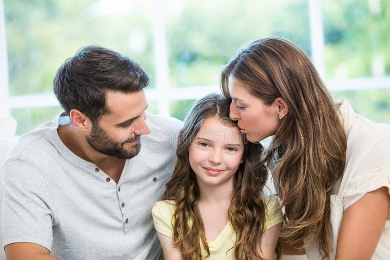 Kyssande dotter för moder medan fader som håller ögonen på dem arkivfoton