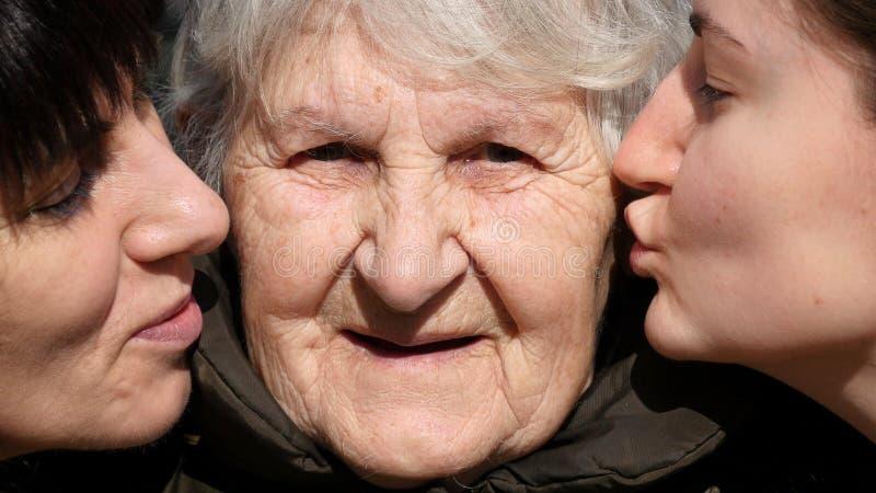 Kyssande farmor för ung flicka och för vuxen kvinna på kinder, farmor som ler och ser till kameran familj tre royaltyfria bilder