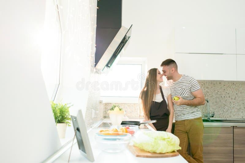 Kyssande frumatlagning för stilig man i kök arkivfoton
