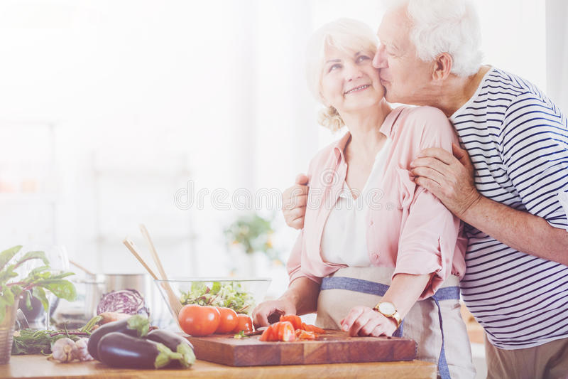 Kyssande kvinna för hög man i köket fotografering för bildbyråer