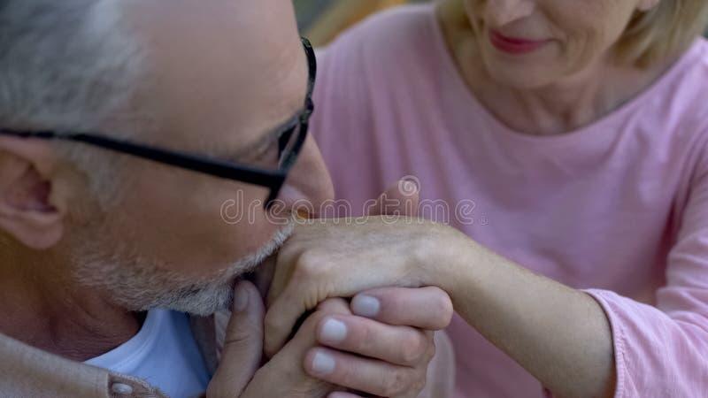 Kyssande kvinnahand för äldre man, romantiskt datum utomhus, förälskade gamla par fotografering för bildbyråer