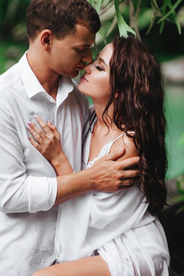 Kyssande lyckliga par, medan koppla av i utomhus- brunnsortsimbass?ng royaltyfri foto