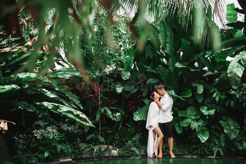 Kyssande lyckliga par, medan koppla av i utomhus- brunnsortsimbass?ng royaltyfri fotografi