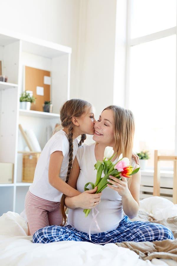 Kyssande mamma f?r flicka arkivfoton