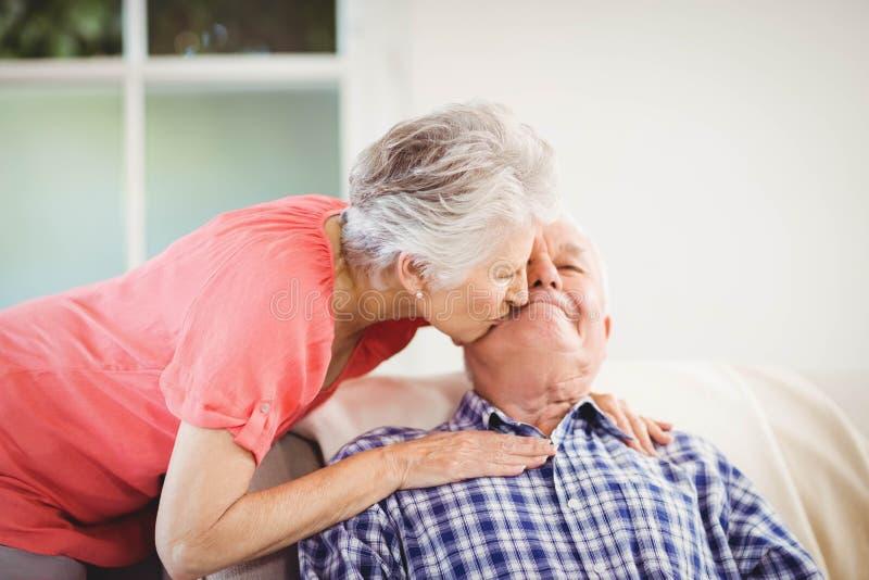 Kyssande man för hög kvinna på kind royaltyfri bild