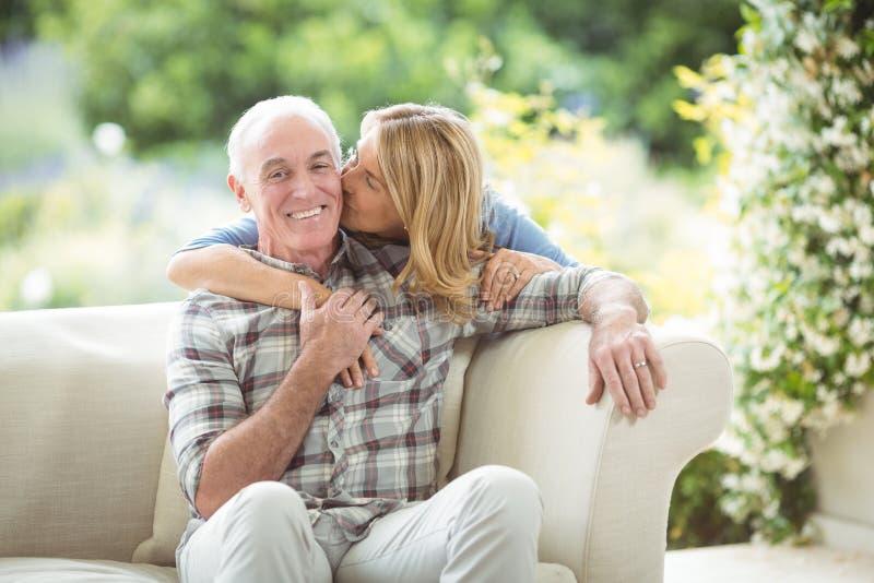 Kyssande man för hög kvinna på kind i vardagsrum royaltyfria bilder