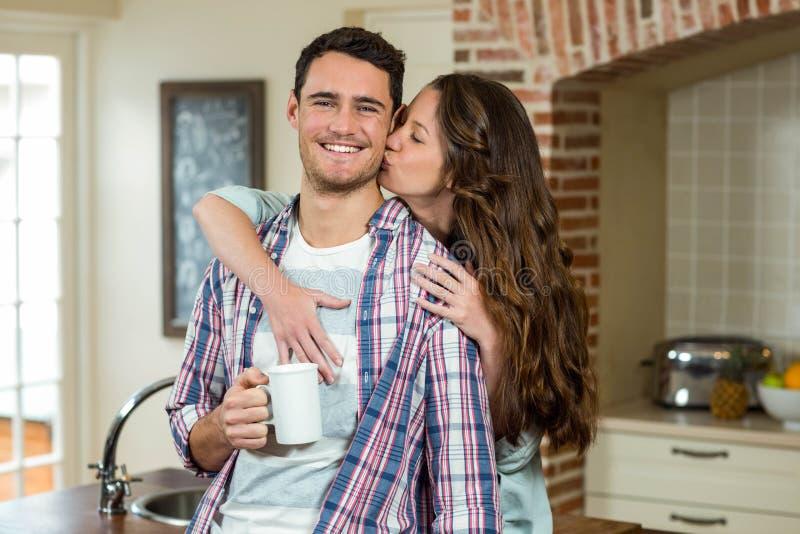 Kyssande man för kvinna bakifrån, medan ha kaffe royaltyfria foton