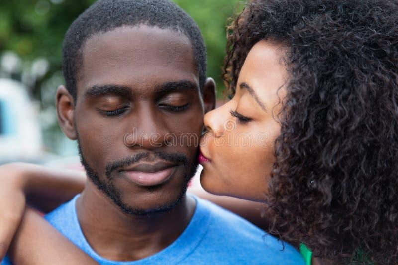 Kyssande pojkvän för afrikansk amerikankvinna fotografering för bildbyråer
