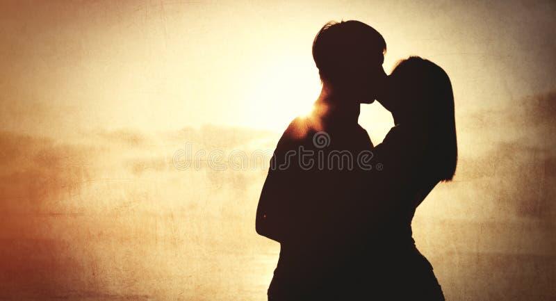 kyssande soluppgång för par arkivbilder