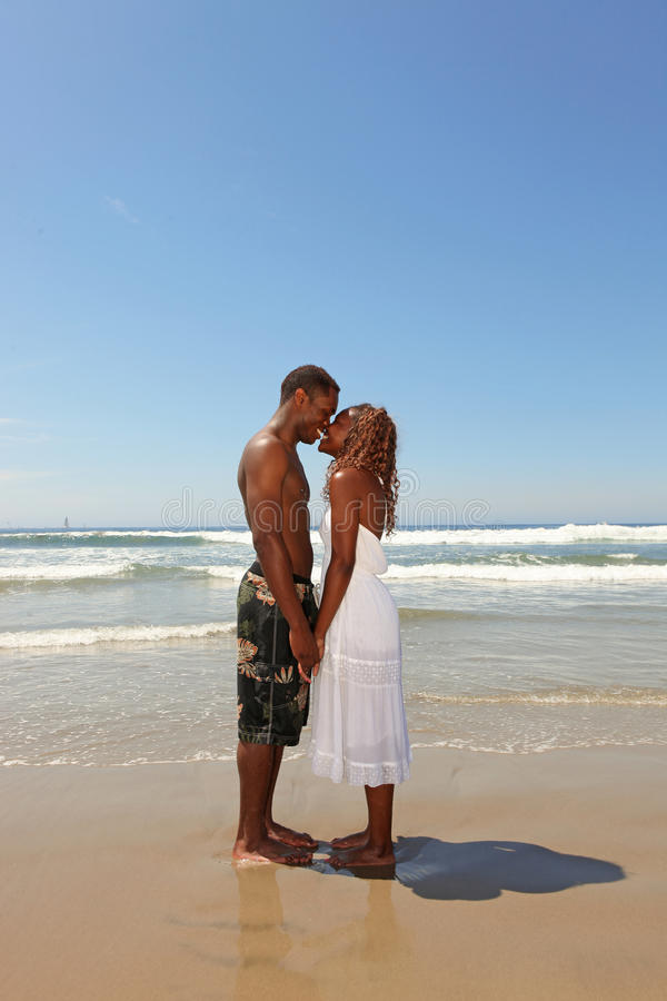 kyssande th för afrikansk amerikanstrandpar royaltyfri foto