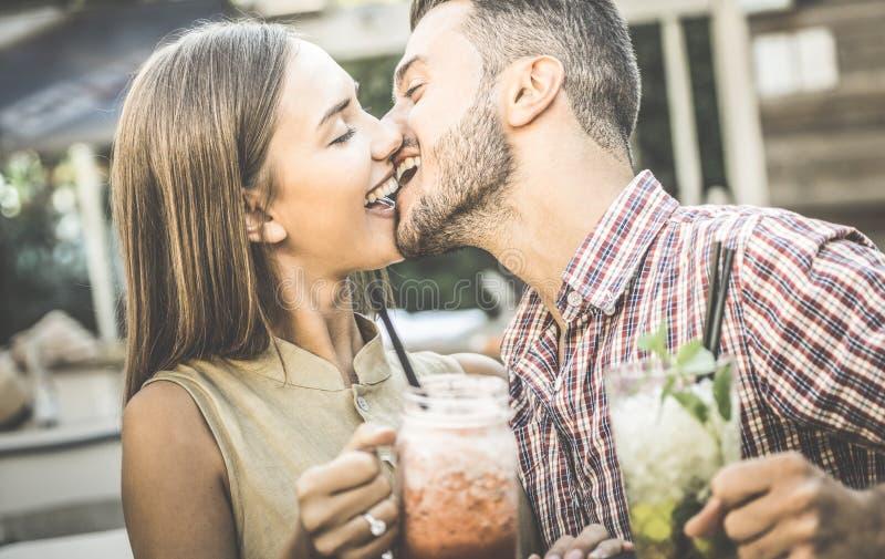 Kyssande ung kvinna för stilig man på modecoctailstången arkivfoto