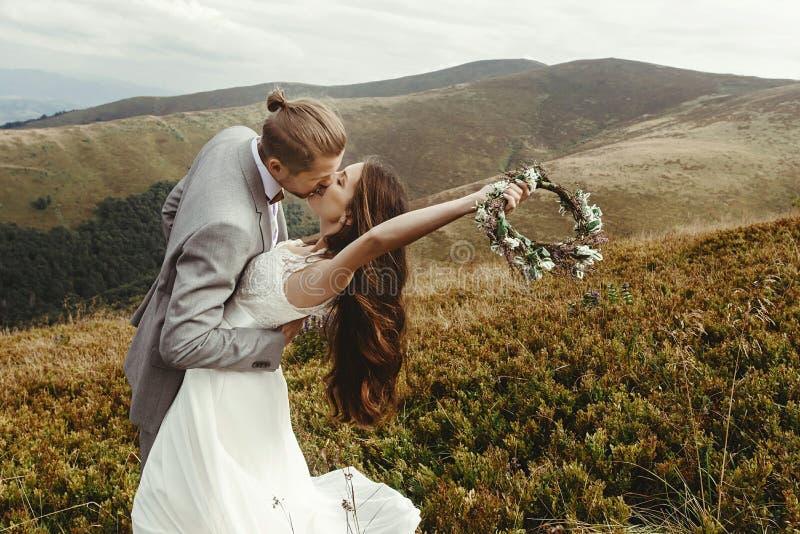 Kyssande ursnygg brud för stilfull brudgum i solljus, perfekt mome royaltyfri foto