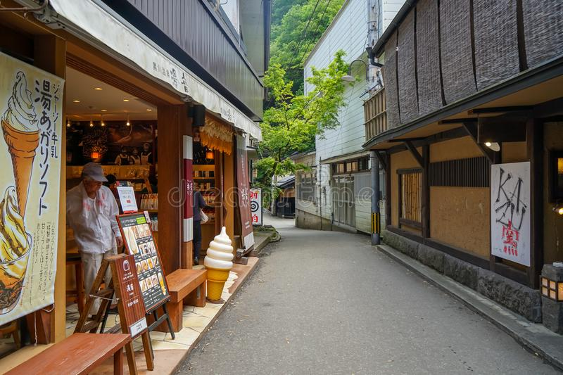 Local vintage street atmosphere with an unidentified man in ice cream shop and restaurant buildings, Kurokawa Onsen town royalty free stock photography