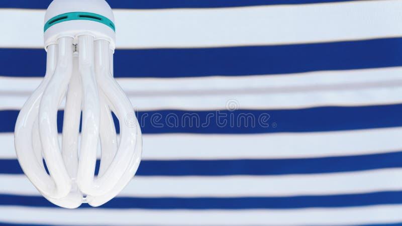 Lámpara ahorro de energía blanca en fondo blanco-azul imagenes de archivo