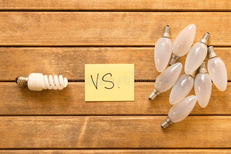 Lámpara ahorro de energía contra Lámpara incandescente El concepto de energía imagenes de archivo