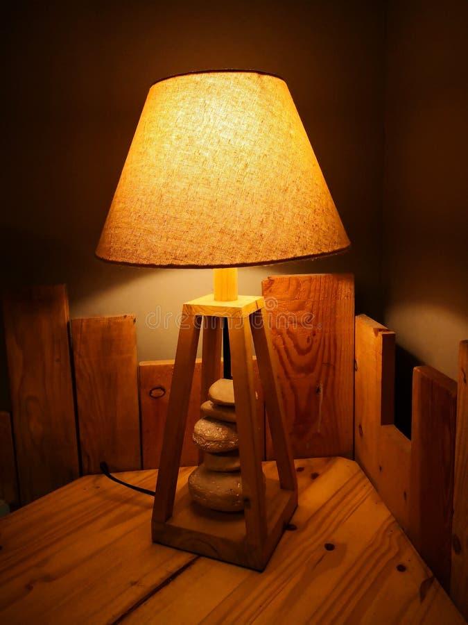 Lámpara amarilla en la tabla de madera imagen de archivo