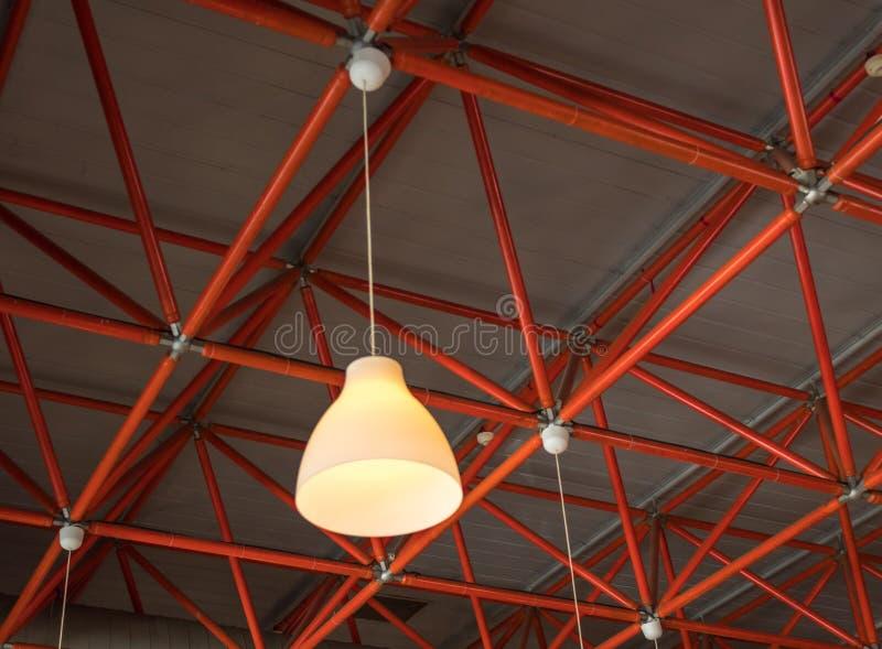 Lámpara amarilla que cuelga de haces rojos industriales del techo imagen de archivo