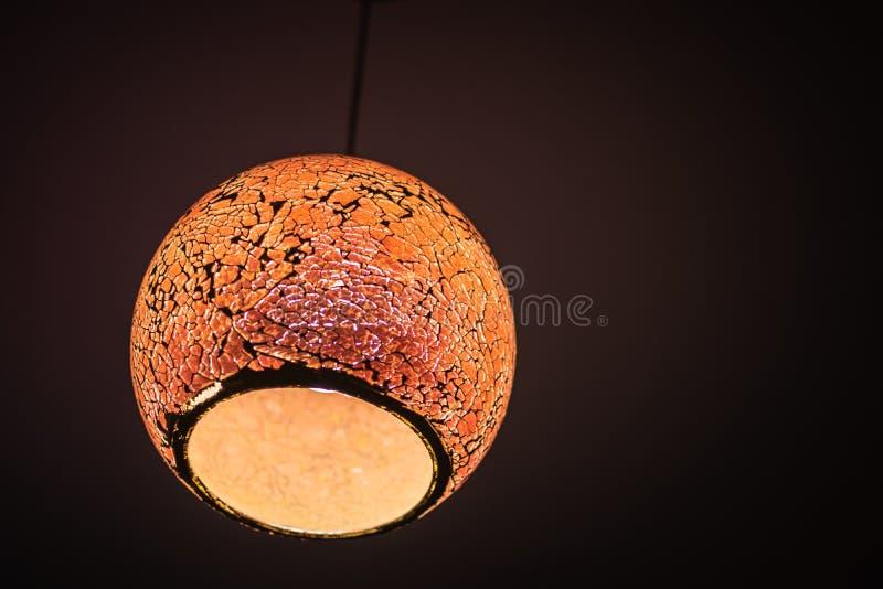 Lámpara anaranjada con el fondo oscuro imagenes de archivo