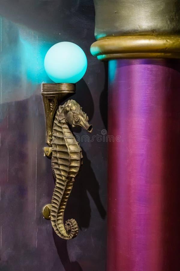 Lámpara animal de la escultura de la vida marina antigua de oro del seahorse con una bombilla azul imágenes de archivo libres de regalías