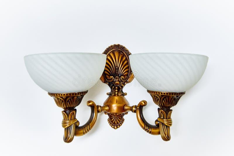 Lámpara blanca con oro en una pared blanca fotografía de archivo libre de regalías