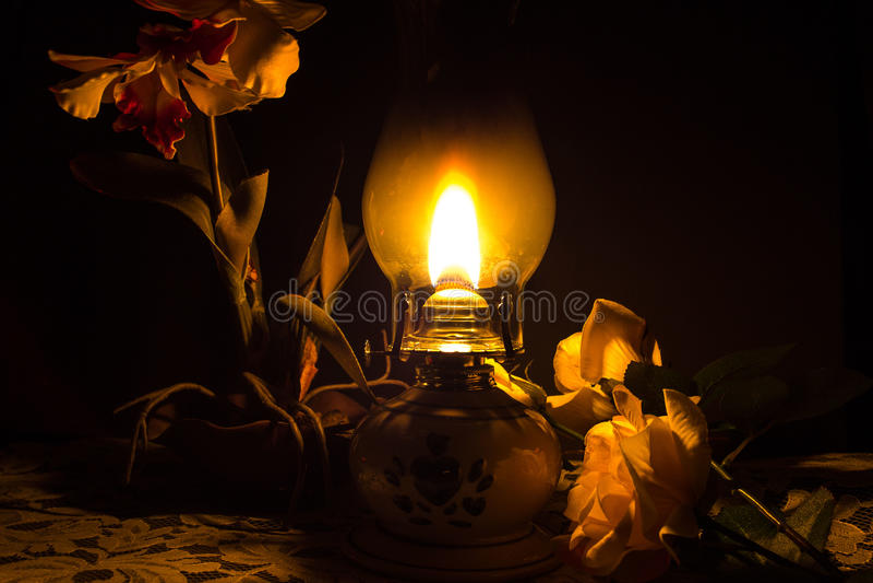 Lámpara de aceite con las flores foto de archivo