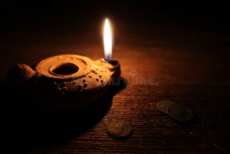 Lámpara de aceite de Oriente Medio y monedas viejas fotos de archivo