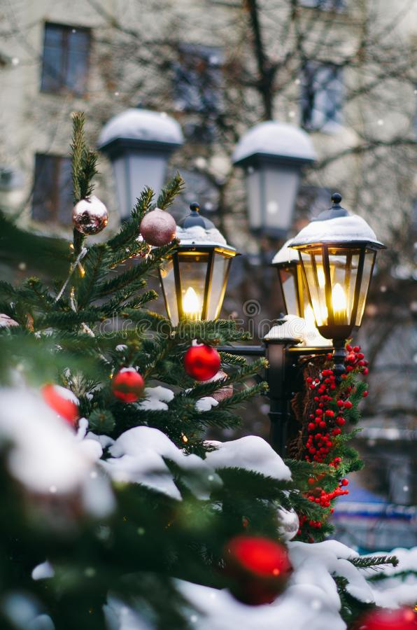 Lámpara de calle adornada con los conos del pino del personal de la Navidad, bayas rojas, manojo del abeto fotografía de archivo libre de regalías
