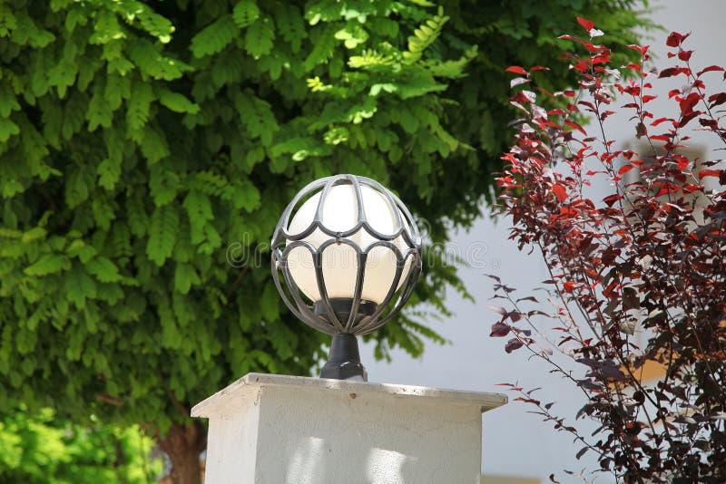 Lámpara de calle bajo la forma de bola en el marco forjado en el sol del verano imagenes de archivo