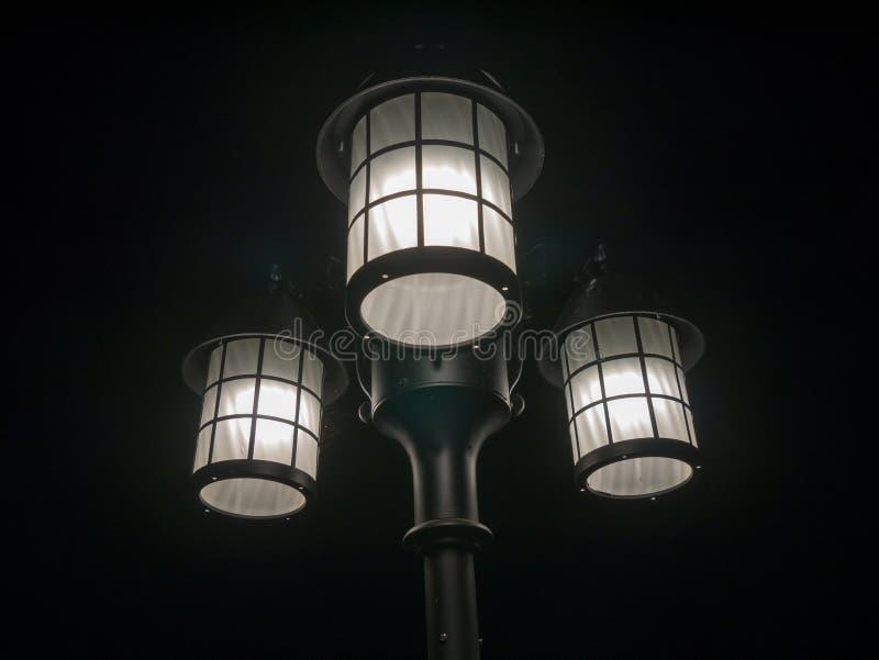 lámpara de calle de 3 cabezas, fondo oscuro foto de archivo