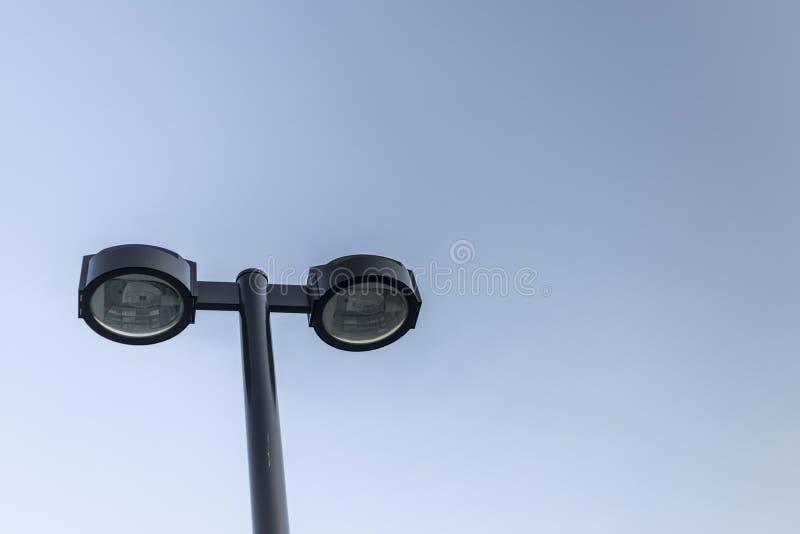 Lámpara de calle doble sobre el cielo azul claro con CopySpace imagenes de archivo